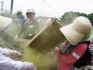 糀を壺に入れる作業